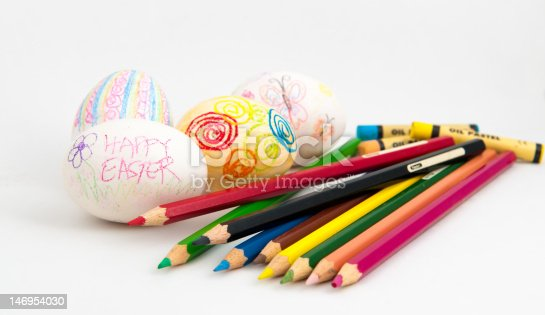 White eggs in the process of being decorated with colour pencils and crayons