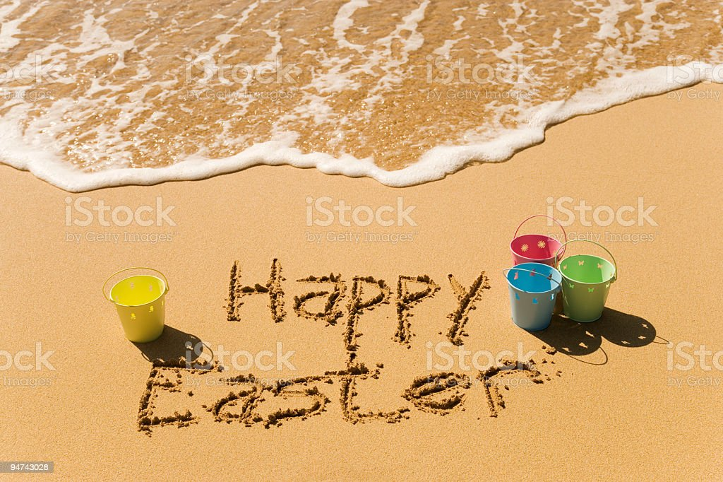 Happy Easter writing at a beach with buckets on the sides royalty-free stock photo