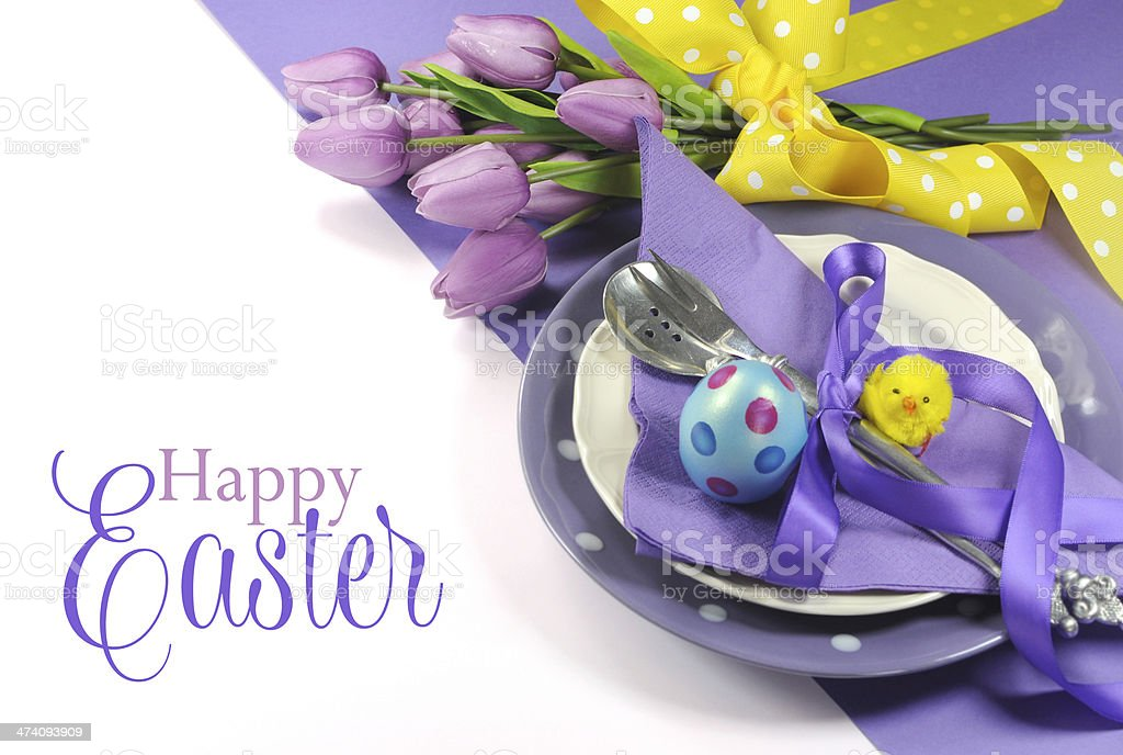 Happy Easter yellow and purple table place setting with text stock photo