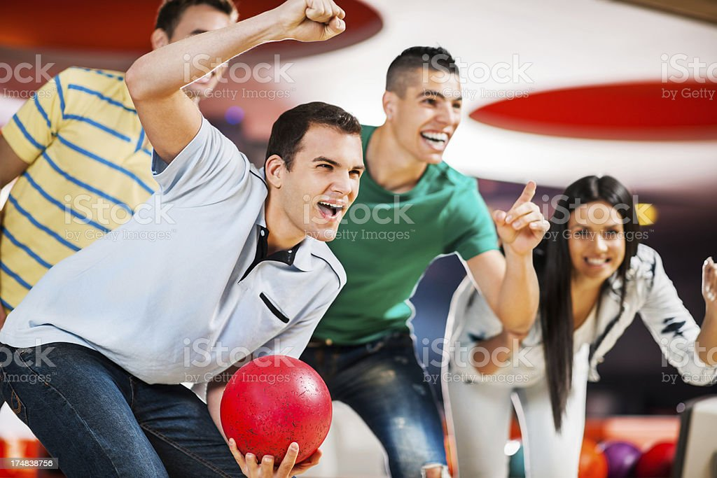 Happy ecstatic friends supporting their bowling team. stock photo