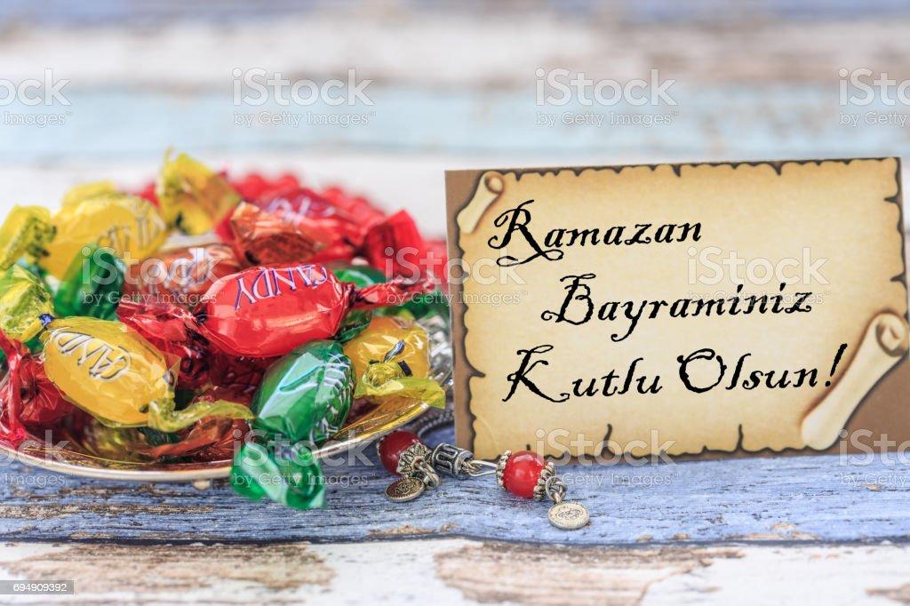 Joyeux Aïd al fitr en turc sur la carte avec des sucreries sur table vintage - Photo