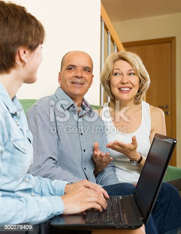584597964 istock photo Happy eldelry couple talking with employee with laptop 500279409