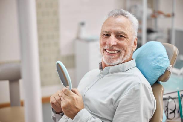 Happy eldelry man sitting in a dental chiar stock photo