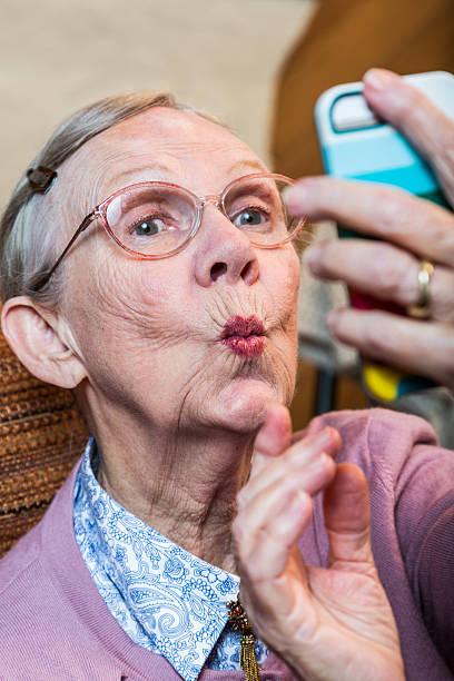 Happy Elder Woman taking Selfie Happy elder woman taking duck face selfie puckering stock pictures, royalty-free photos & images