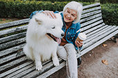 istock Happy elderly Caucasian lady palming nice dog in park 1186942795
