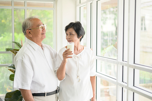 Happy elderly couple drinking milk and spending time together at home, health and retirement concept