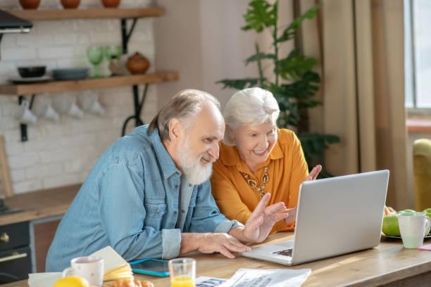 Glückliches älteres Paar mit einem Videoanruf suchen beteiligt – Foto