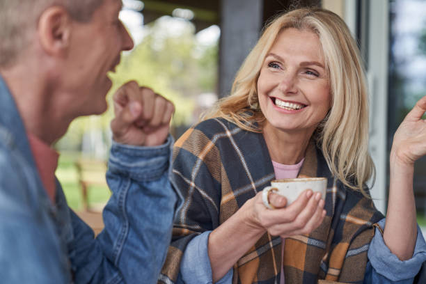 Happy elderly couple talking with cups of hot drinks stock photo