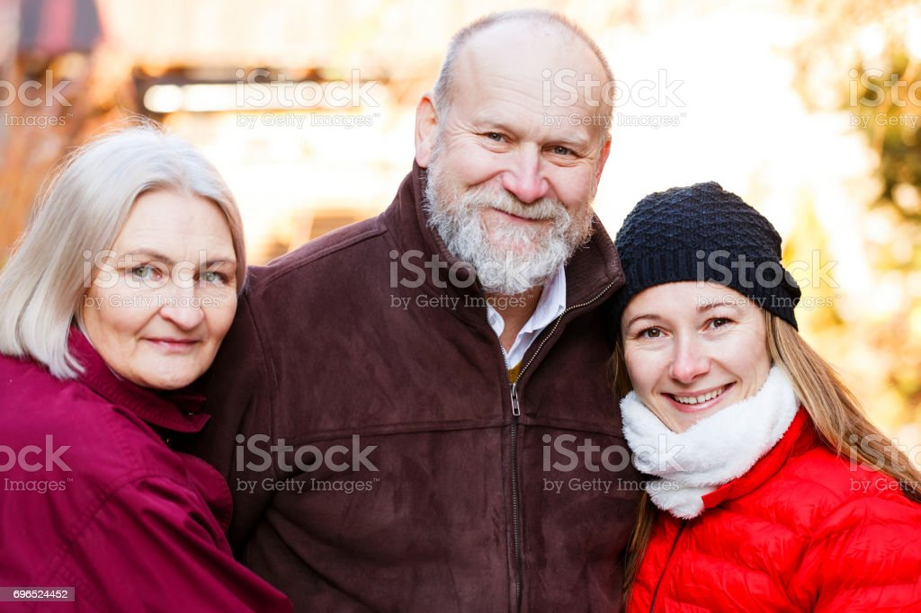 Happy elderly couple with the young carer stock photo