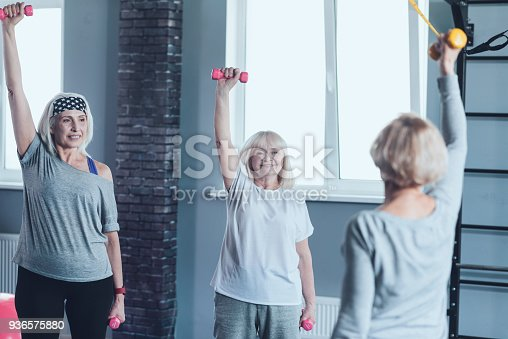936573360 istock photo Happy elderly ladies stretching hands with dumbbells at gym 936575880