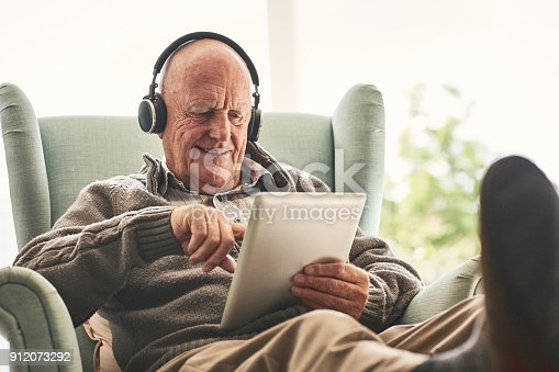 Happy elderly man relaxing on a chair at home and listening to music on digital tablet with headphones