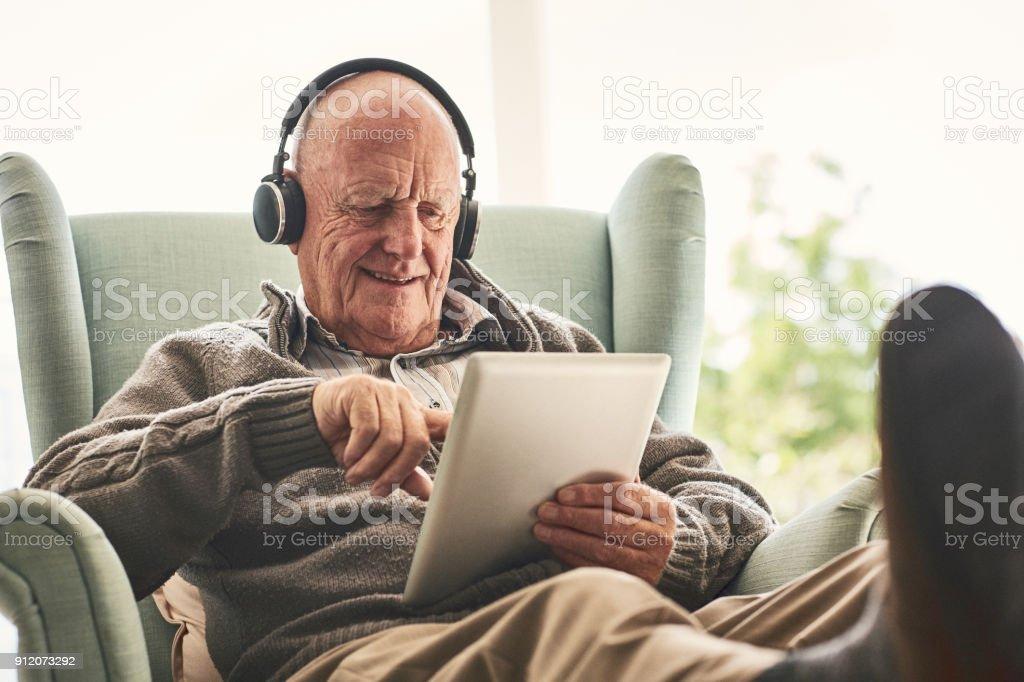 Glücklicher älterer Mann zu Hause mittels digital-Tablette – Foto