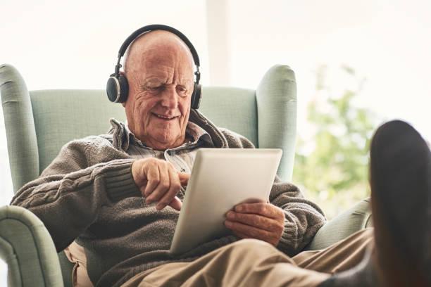 o homem idoso feliz em casa usando tablet digital - 70 anos - fotografias e filmes do acervo