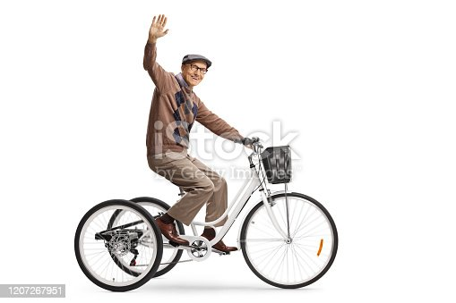 Happy elderly man riding a tricycle and waving at camera isolated on white background