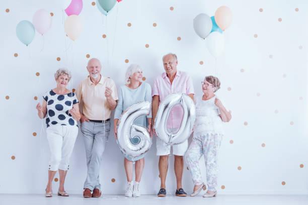glückliche ältere menschen halten ballons - rentenpunkte stock-fotos und bilder