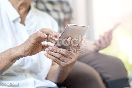 istock Happy elderly senior people society lifestyle technology concept. Ageing Asia women using tablet smartphone or mobile phone share social media together in wellbeing county home. 1156215857
