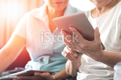 Happy elderly twin senior people society lifestyle with technology concept. Ageing Asia women using tablet  and smartphone share social media together in wellbeing county home.