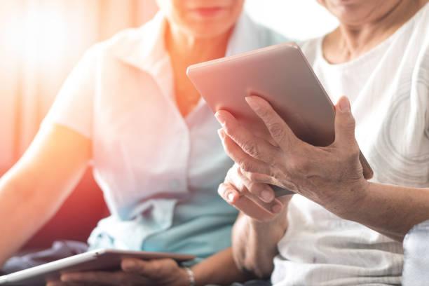 기술 컨셉으로 행복한 노인 쌍둥이 노인 사회 라이프 스타일. 태블릿과 스마트폰을 사용하는 아시아 여성들은 웰빙 카운티 가정에서 소셜 미디어를 함께 공유합니다. - 디지털 태블릿 사용하기 뉴스 사진 이미지