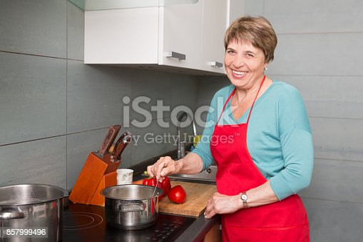 istock Happy elderly woman cooking  in kitchen at home 857999496