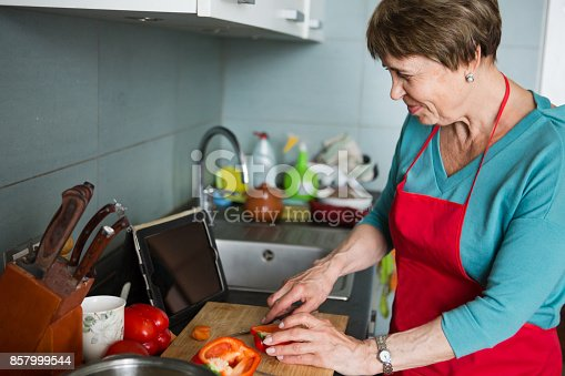 istock Happy elderly woman cooking  in kitchen at home 857999544