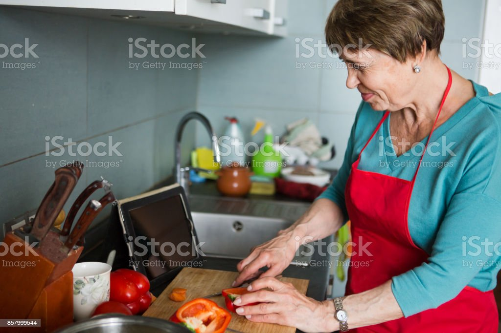 Happy elderly woman cooking  in kitchen at home stock photo