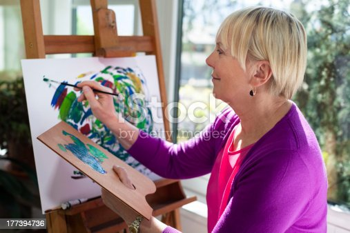 istock Happy elderly woman painting for fun at home 177394736