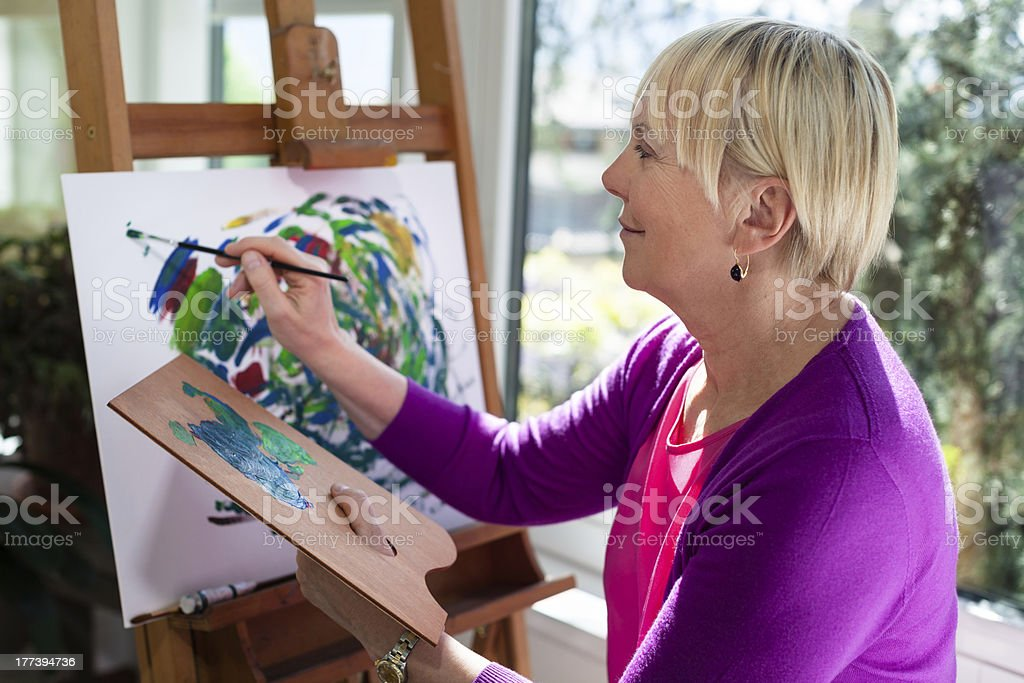 Happy elderly woman painting for fun at home stock photo