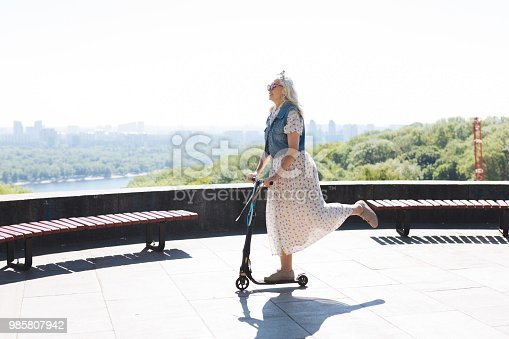 istock Happy elderly woman riding a scooter 985807942