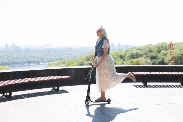 Happy elderly woman riding a scooter stock photo