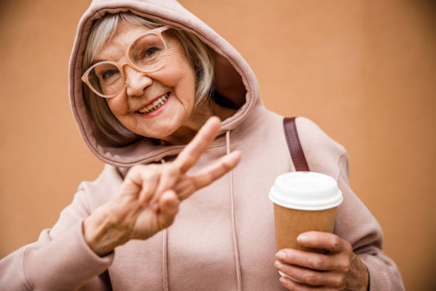 Happy elderly woman showing V sign stock photo Jolly aged female in hood and glasses is demonstrating peace gesture while drinking coffee cool attitude stock pictures, royalty-free photos & images