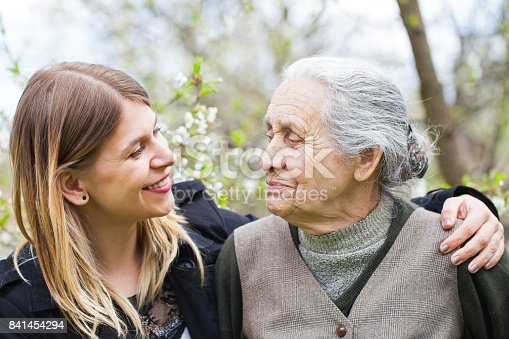 istock Happy elderly woman with carer outdoor - springtime 841454294