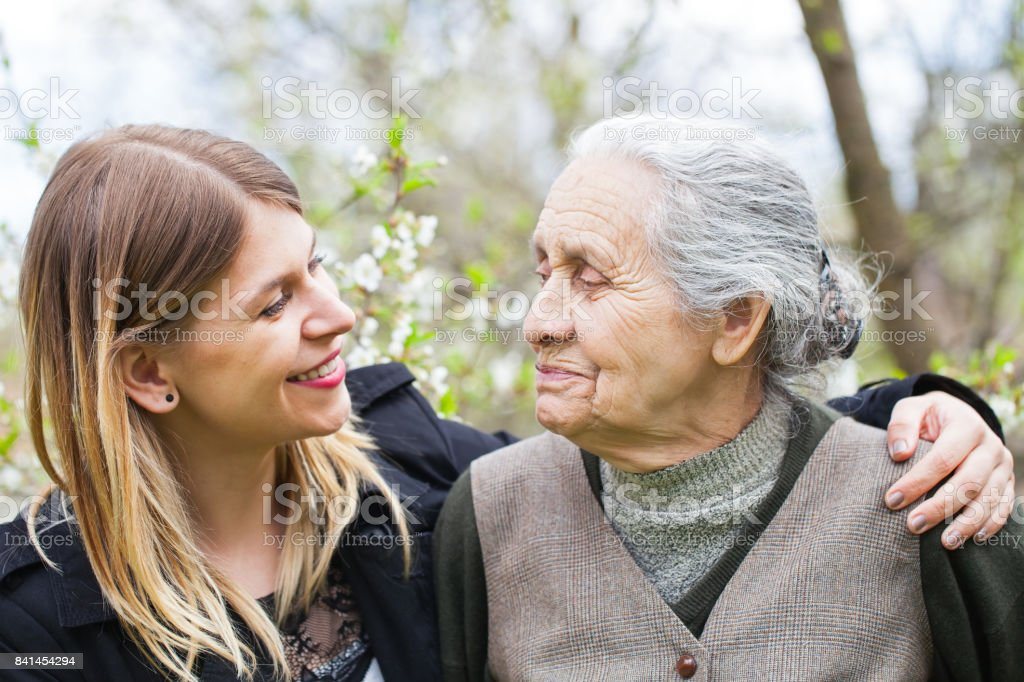 Happy elderly woman with carer outdoor - springtime stock photo