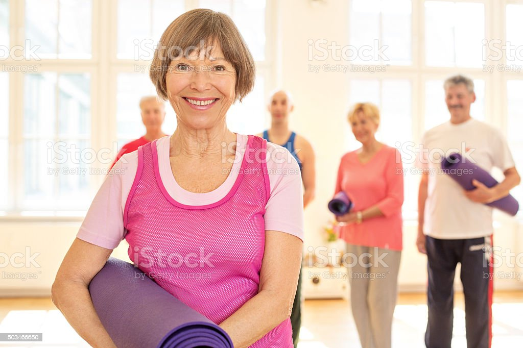 Happy elderly woman with exercise mat in a gym stock photo