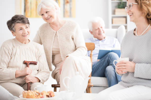 Happy elderly women drinking tea Happy elderly women having fun together while eating dessert and drinking tea retirement community stock pictures, royalty-free photos & images
