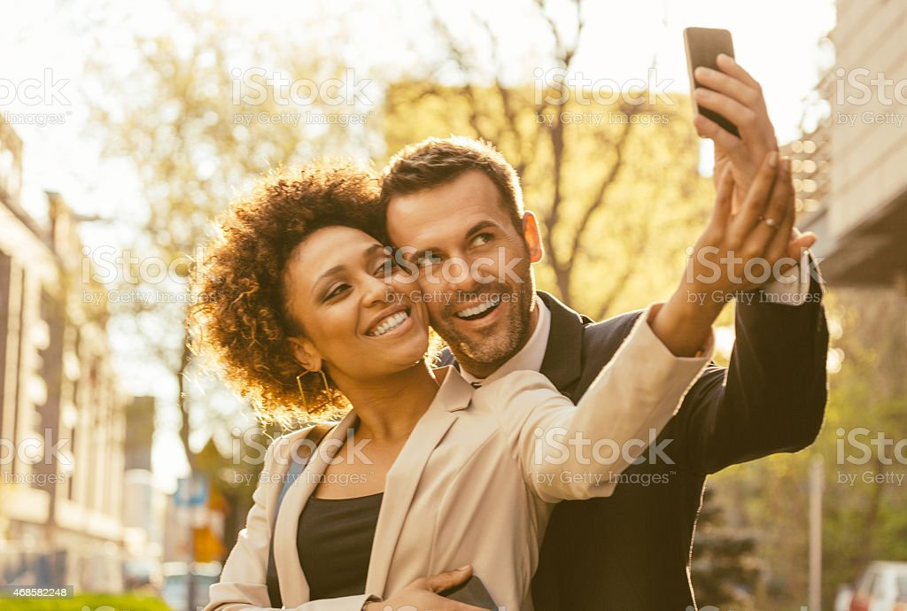 Happy elegance adult couple talking selfie outdoor Cheerful adul couple - afro amercian woman and caucasian man embracing and taking selfie using smart phone outdoor at sunset. Close up of faces. 2015 Stock Photo