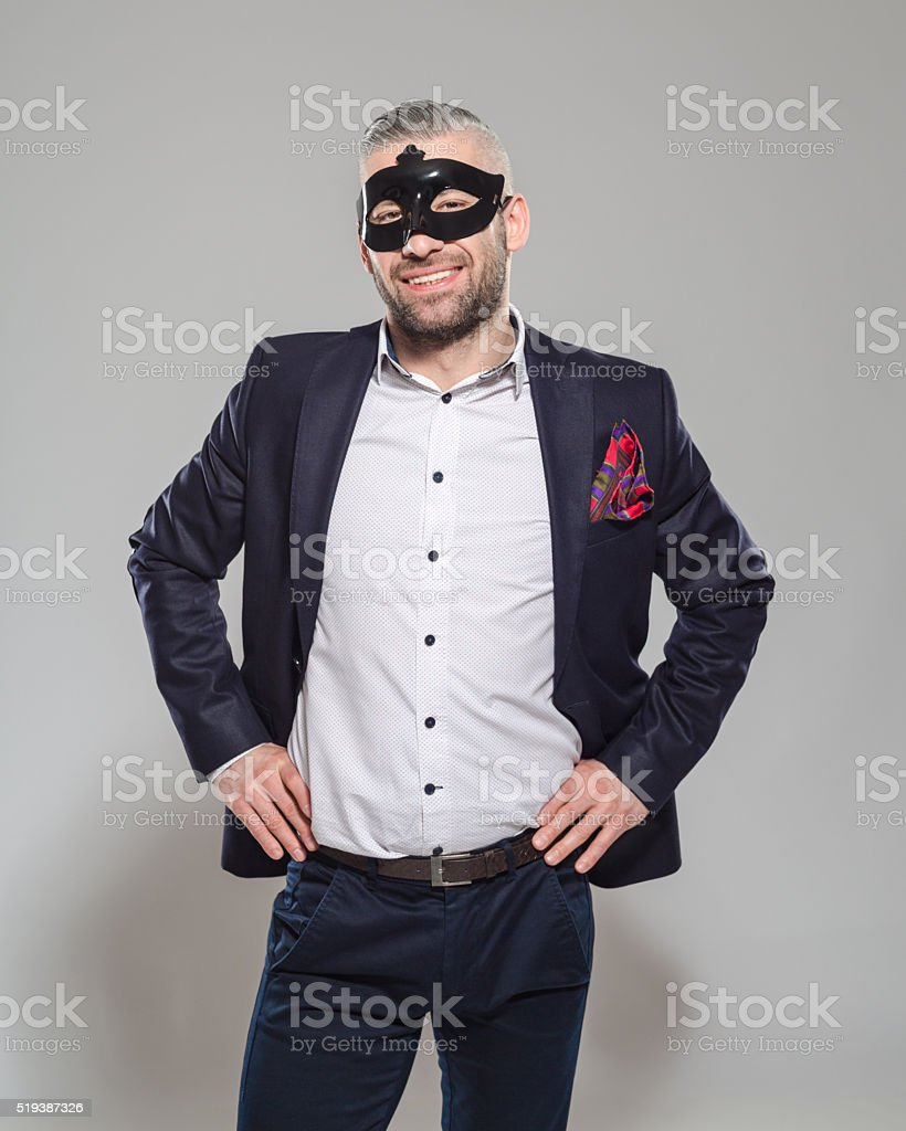 Happy elegant bearded man wearing carnival mask Portrait of elegant bearded businessman wearing jacket and carnival mask. Standing against grey background and laughing at camera. Studio shot, one person.  Adult Stock Photo