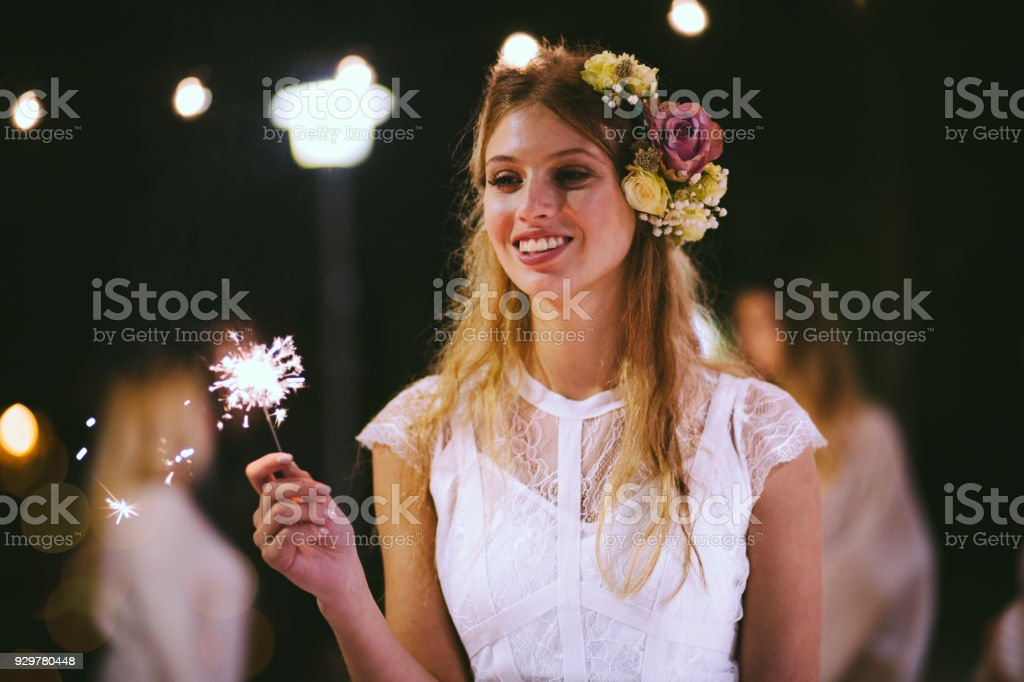 Happy elegant bride celebrating with sparklers at wedding party stock photo
