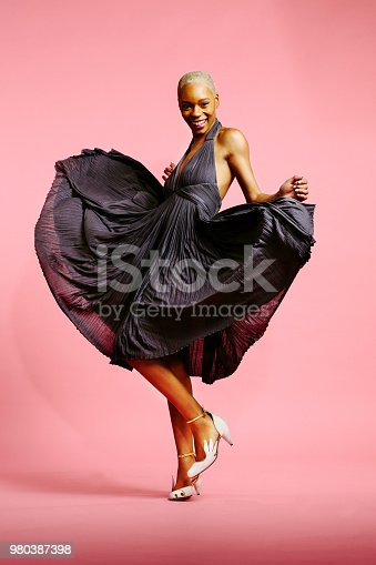 Portrait of a beautiful young woman with very short platinum hair in pleated dress dancing, isolated on pink studio background