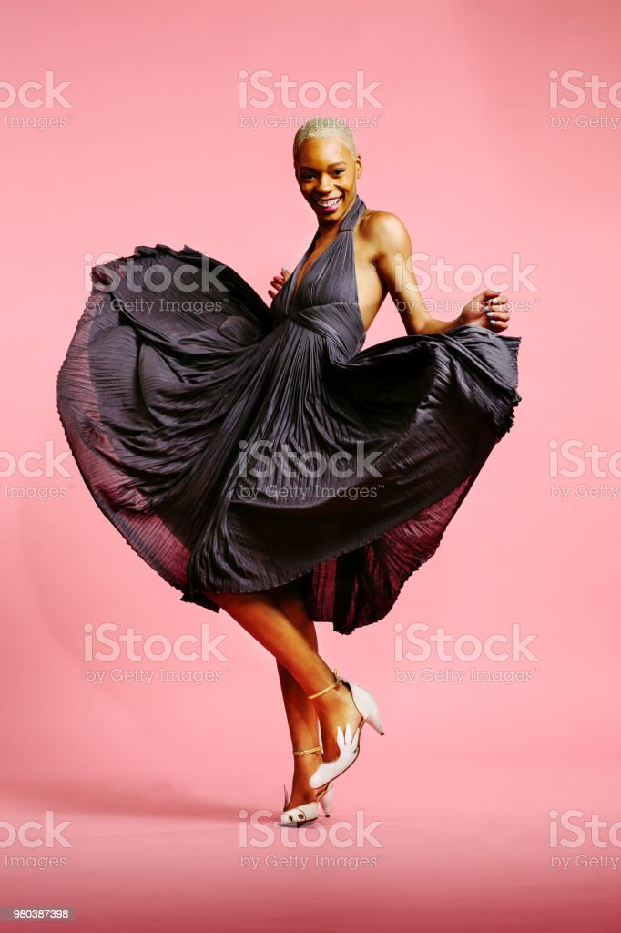 Happy elegant girl dancing with dress in the air stock photo