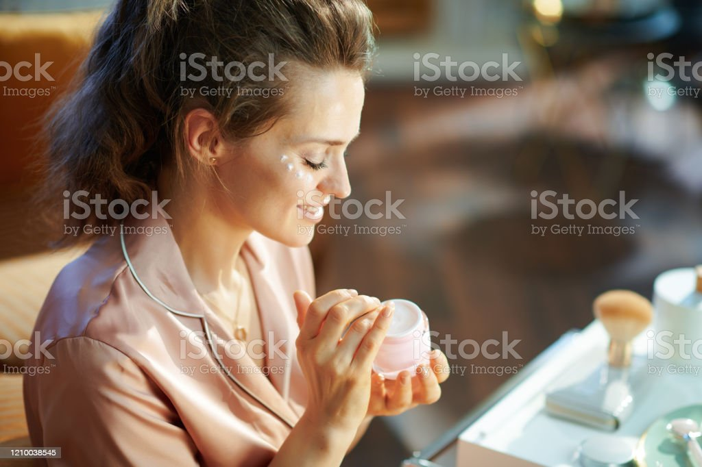 happy elegant housewife with cosmetic jar applying eye cream happy elegant housewife in pajamas with pink cosmetic jar applying eye cream in the modern living room in sunny winter day. Adult Stock Photo