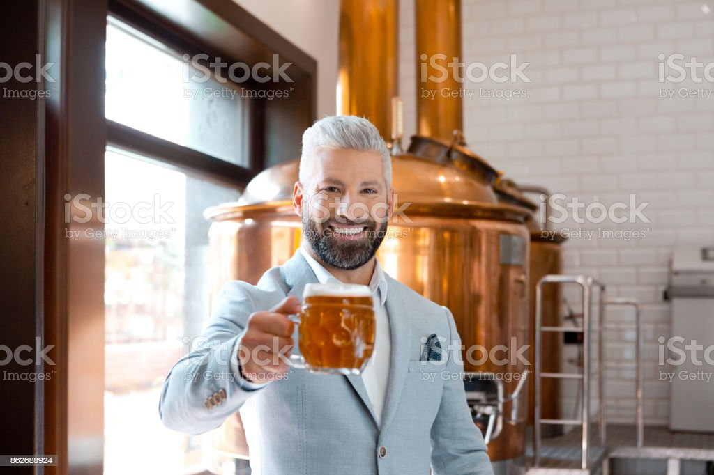 Happy elegant man holding a beer mug in microbrewery The microbrewery owner standing in front to copper vat and holding beer mug, toasting at the camera. Selective focus. Adult Stock Photo