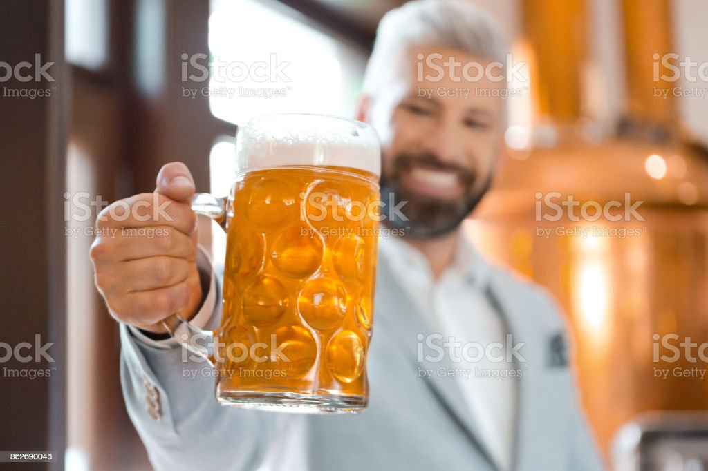 Happy elegant man holding a beer mug in microbrewery The microbrewery owner standing in front to copper vat and holding beer mug, toasting at the camera. Focus on the mug. Adult Stock Photo