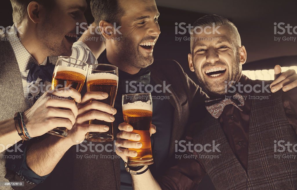 Happy elegant men toasting with beer stock photo