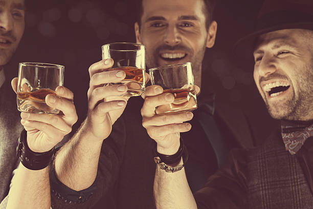happy elegant men toasting with whiskey - whiskey stock photos and pictures