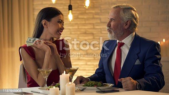 488389267istockphoto Happy elegant mistress holding dollars in hands looking at elderly man, present 1137645905