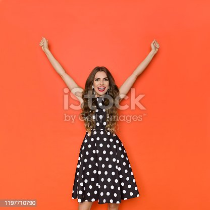 500150419istockphoto Happy Elegant Woman In Cocktail Dress Is Standing With Arms Raised 1197710790