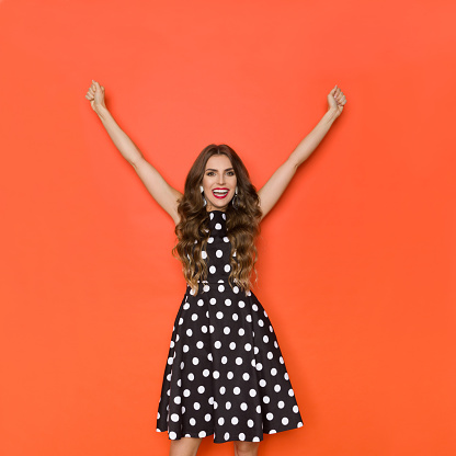 500150419 istock photo Happy Elegant Woman In Cocktail Dress Is Standing With Arms Raised 1197710790