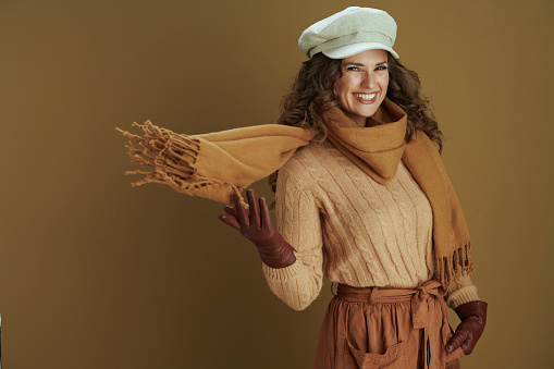 Hello september. happy elegant 40 years old housewife in sweater with leather gloves against brown background.