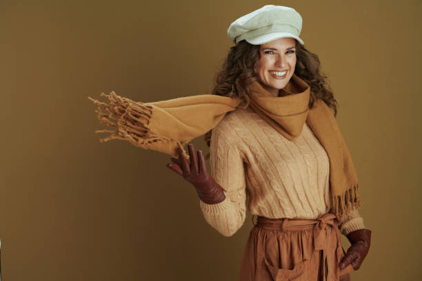 happy elegant woman in sweater against brown background stock photo