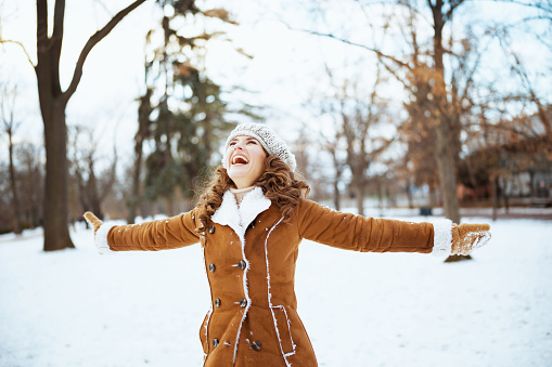 happy elegant woman with mittens in a knitted hat and sheepskin coat rejoicing outside in the city park in winter.